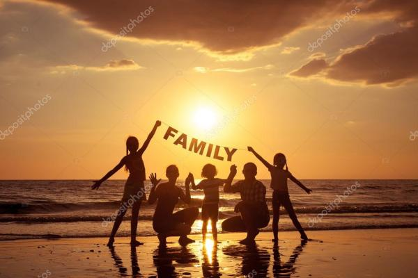 Happy family standing on the beach at the sunset time ...