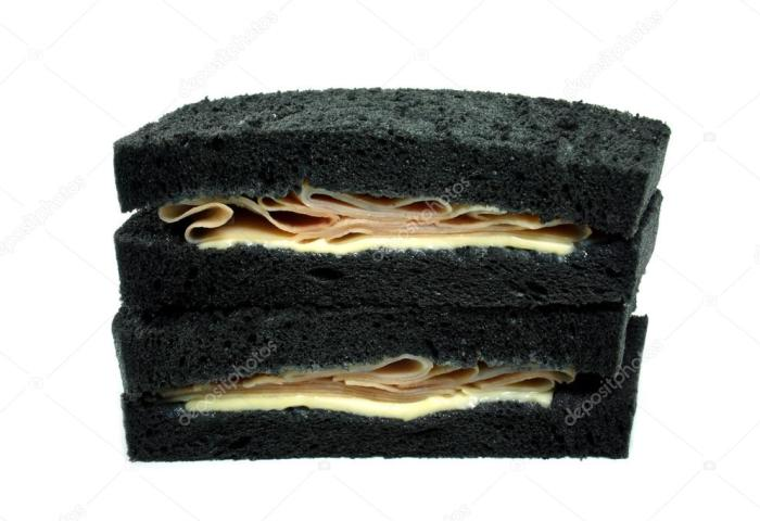 Black Bread Sandwich With Ham And Cheese Stock Photo