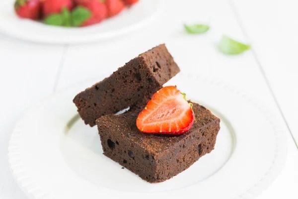 Шоколадний торт з тістечок на білі таріль з strawberrie ...