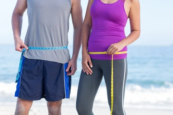 Couple measuring their waist Lose Weight Running