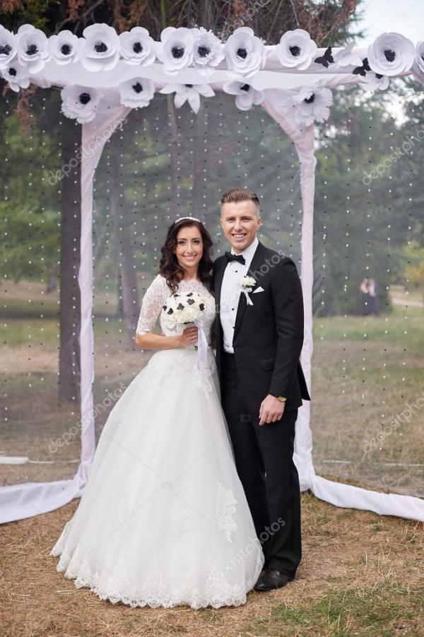 Novia y el novio están parados cerca de arco en la ...