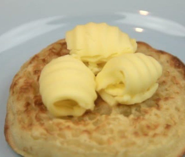 Curls Of Butter Being Being Spread On A Hot English Crumpet With A Knife
