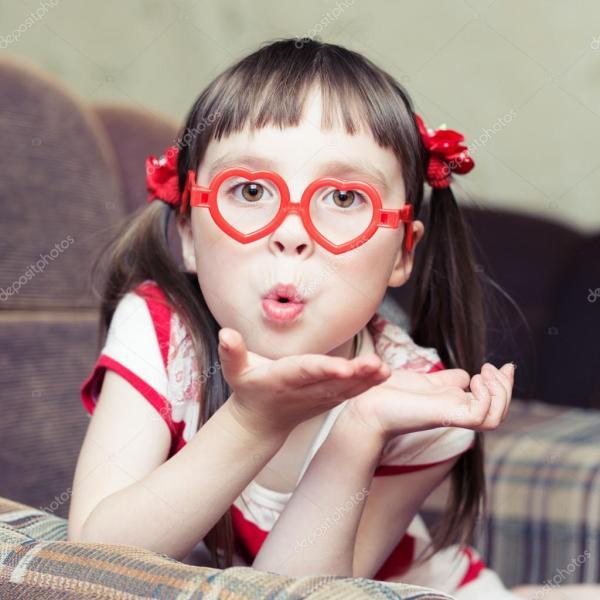 Милая маленькая девочка в очках в форме сердца посылает ...