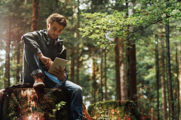 Молодой человек, с помощью цифрового планшета в лесу ...