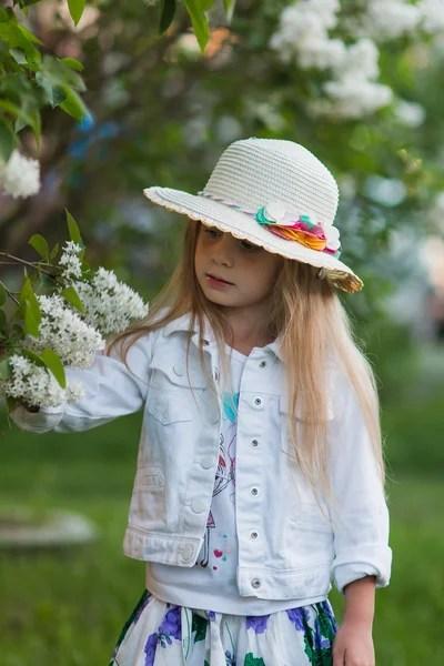 Милая улыбающаяся нарядная девочка на прогулке в цветущем ...