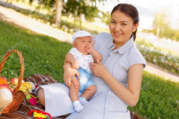 милый маленький мальчик с матерью на пикник в парке летом ...