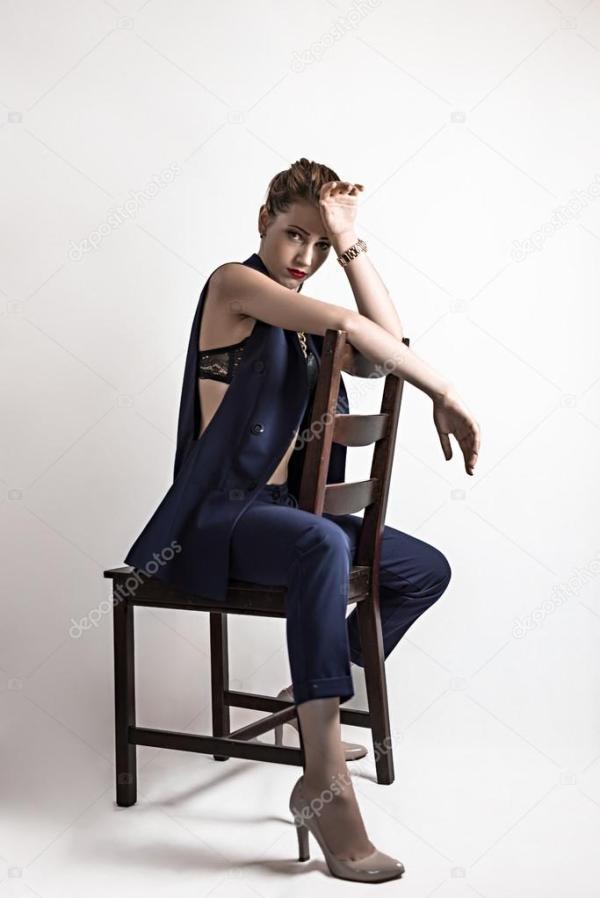 девушка позирует на стуле в студии — Стоковое фото ...