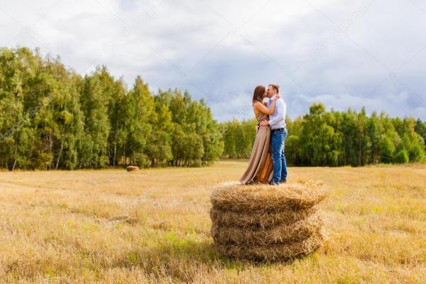Пара влюбленных молодых людей, отдыхающих на стоге сена ...
