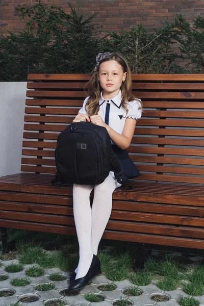Симпатичная школьница в форме на площадке Стоковое фото