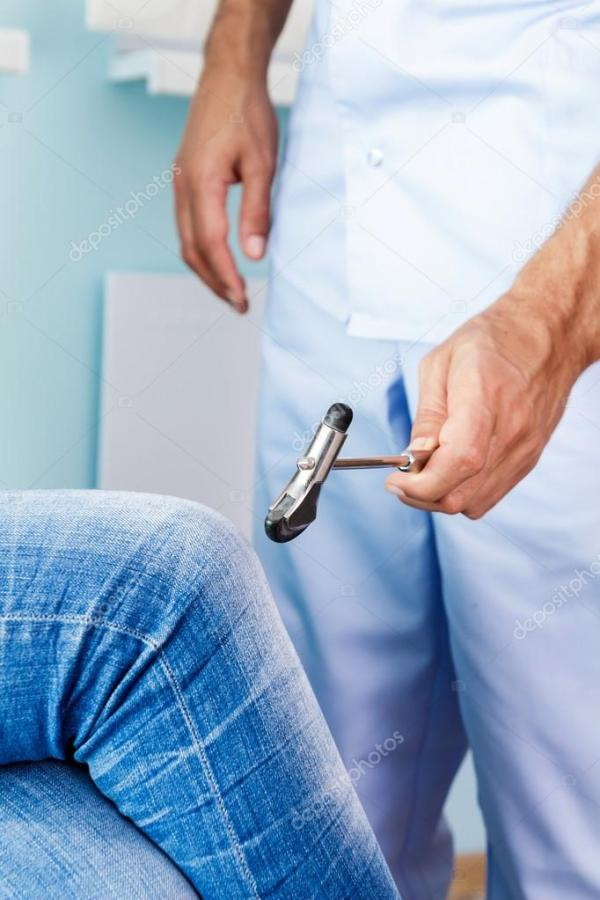 невролог проверяет рефлексы, забивая колено. Врач ...