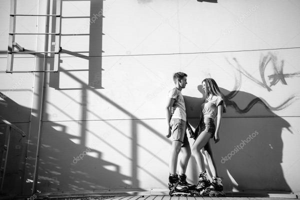 Влюбленная пара на роликах рядом с лестницей на улице. Бла ...
