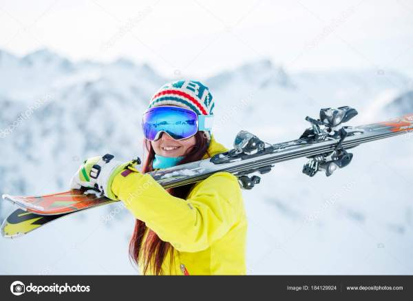 Портрет улыбается женщина в маске с лыжами на ее плече ...