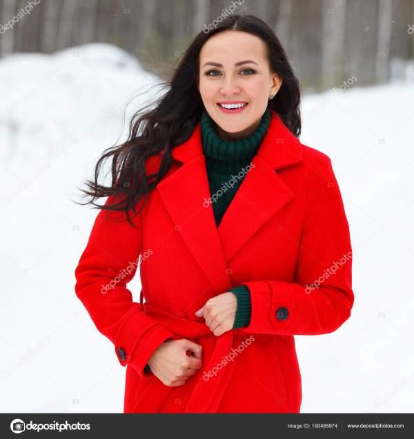 Довольно молодая улыбается женщина в красной шубе ...