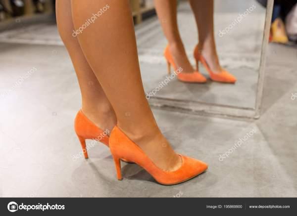 Ноги женщины в туфлях на высоком каблуке у зеркала ...