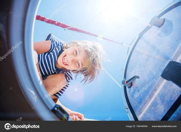 Мальчик на борту парусной яхты в летнем круизе ...