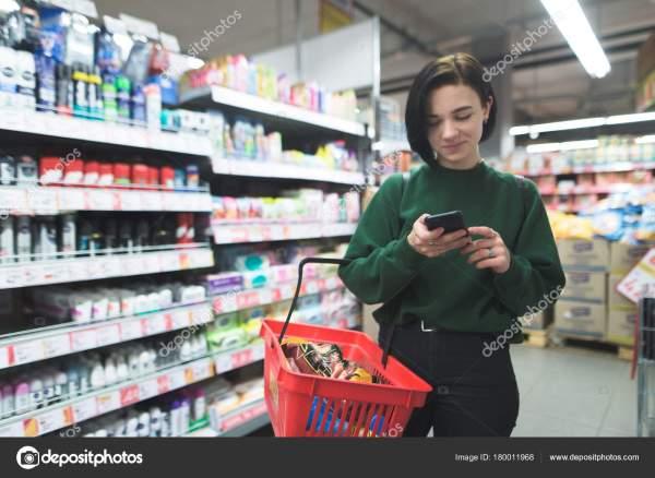 Позитивные девушка использует телефон в супермаркете ...