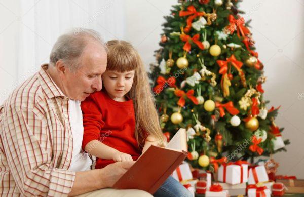 Пожилой мужчина, читать книгу с внучкой в гостиной ...