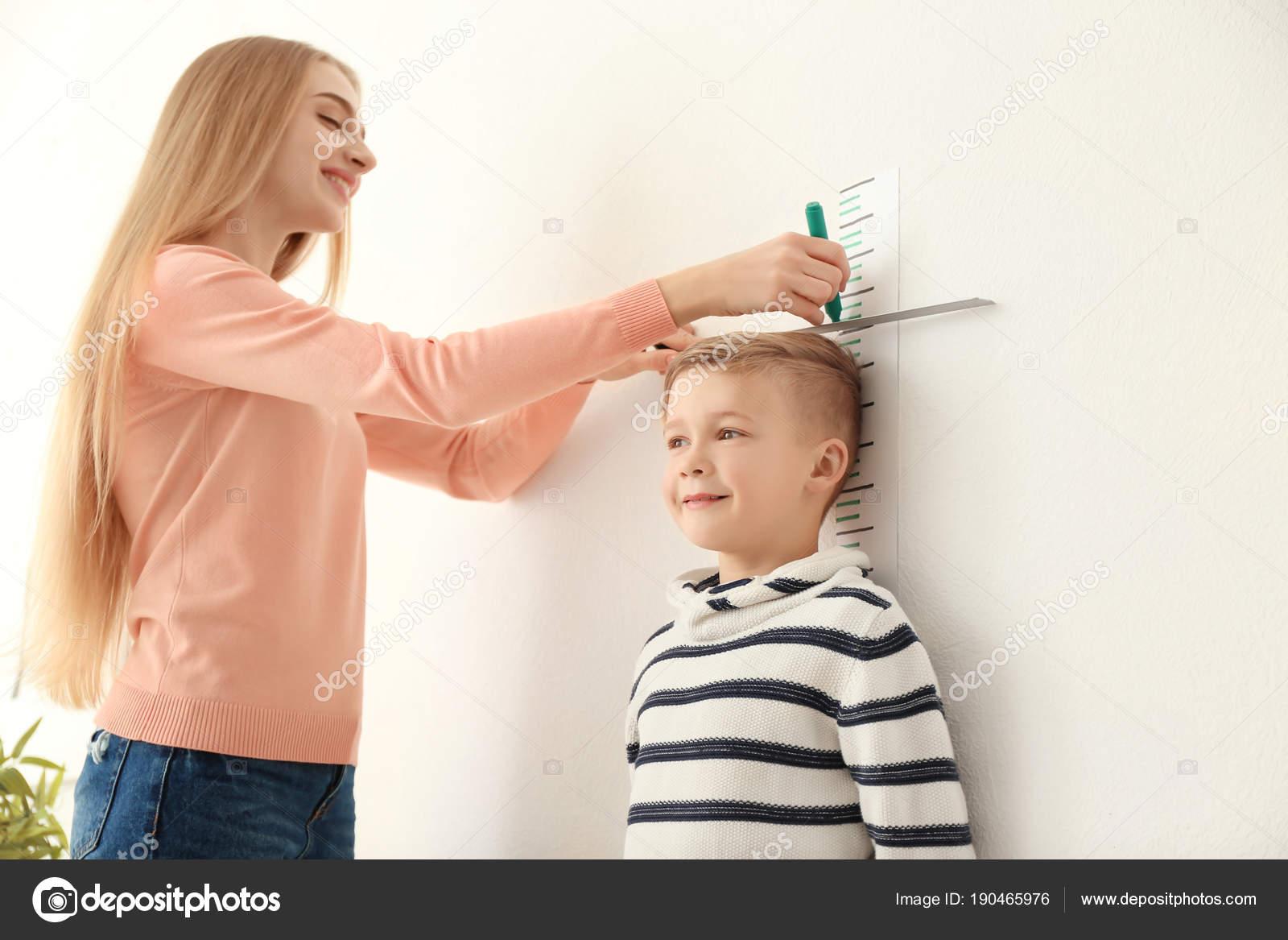 Woman Measuring Height Of Little Boy
