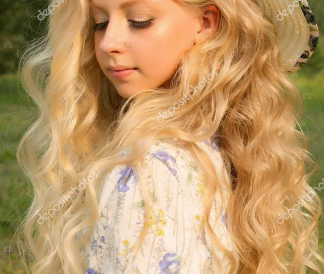 Beautiful Charming Long Curly Blonde Hair Teenage Girl Wearing A Long Light Dress And A Hat Outdoors Smiles In Sunlight Copy Space