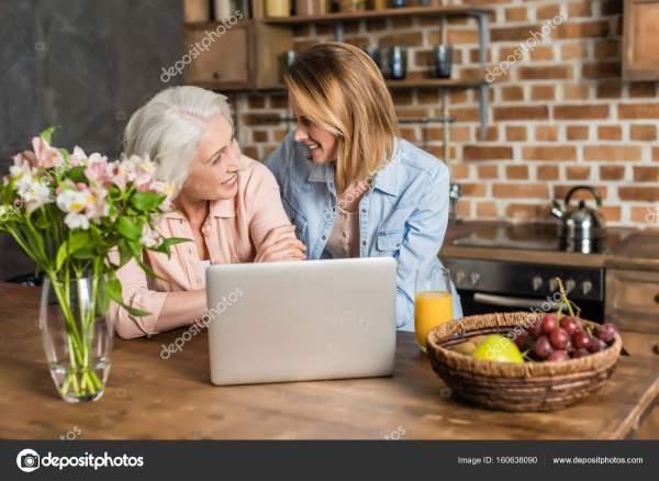 Женщины, используя ноутбук в кухне — Стоковое фото ...