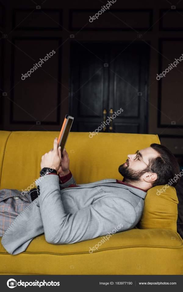 Бородатый Человек Использованием Цифрового Планшета Лежа ...