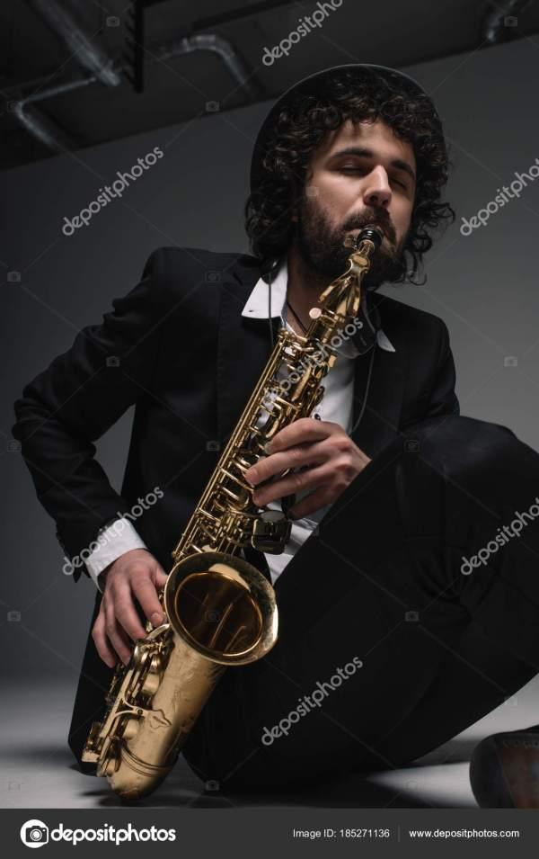 Художественный музыкант играет саксофон сидя на полу