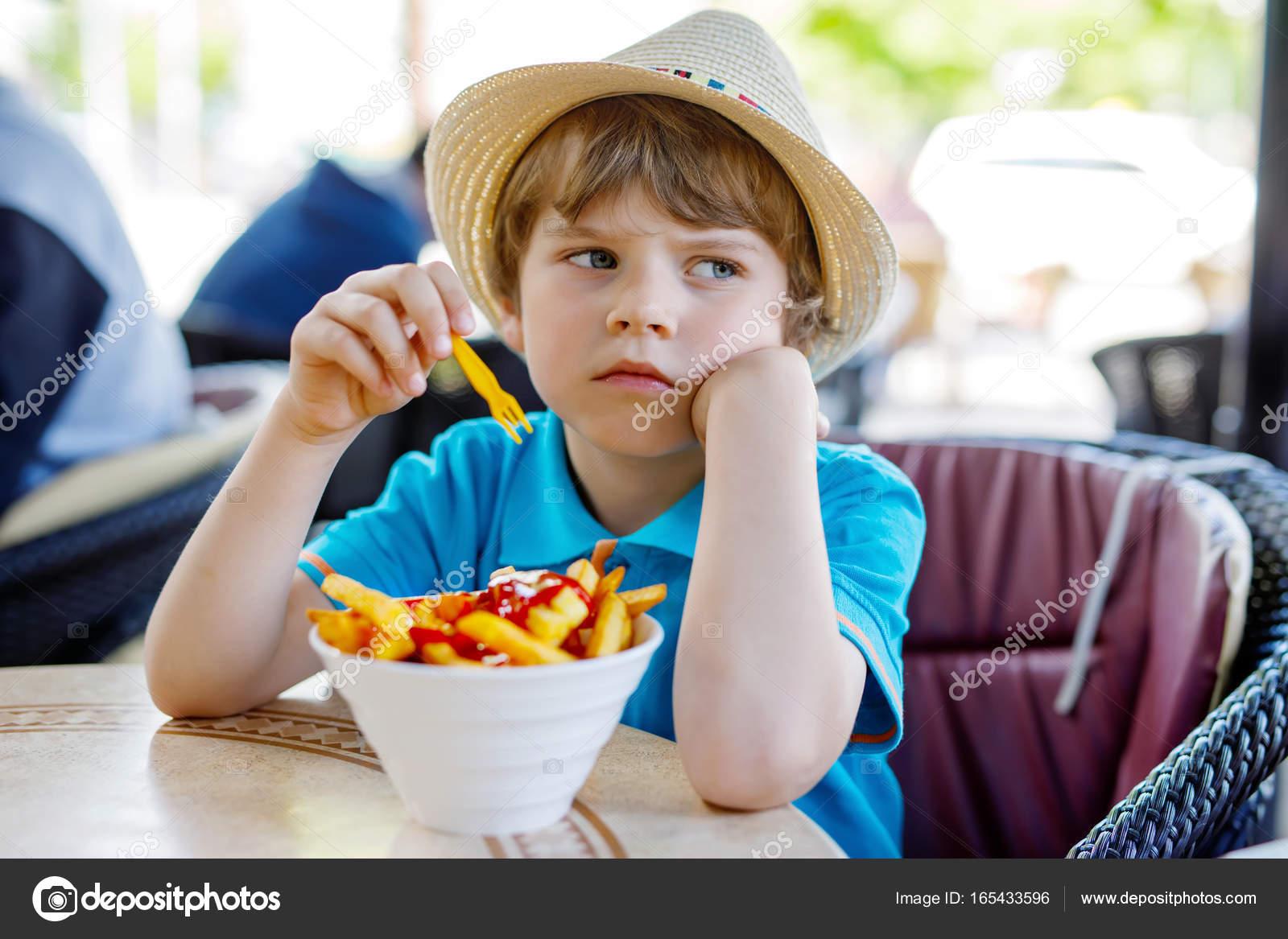 Cute Healthy Preschool Kid Boy Eats French Fries Potatoes