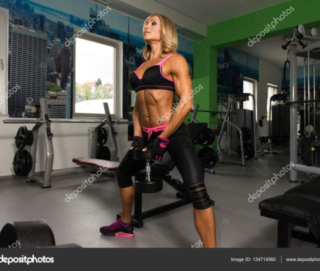 Mature Woman Exercising Butt With Dumbbells In The Gym And Flexing Muscles Muscular Athletic Bodybuilder Fitness Model Photo By
