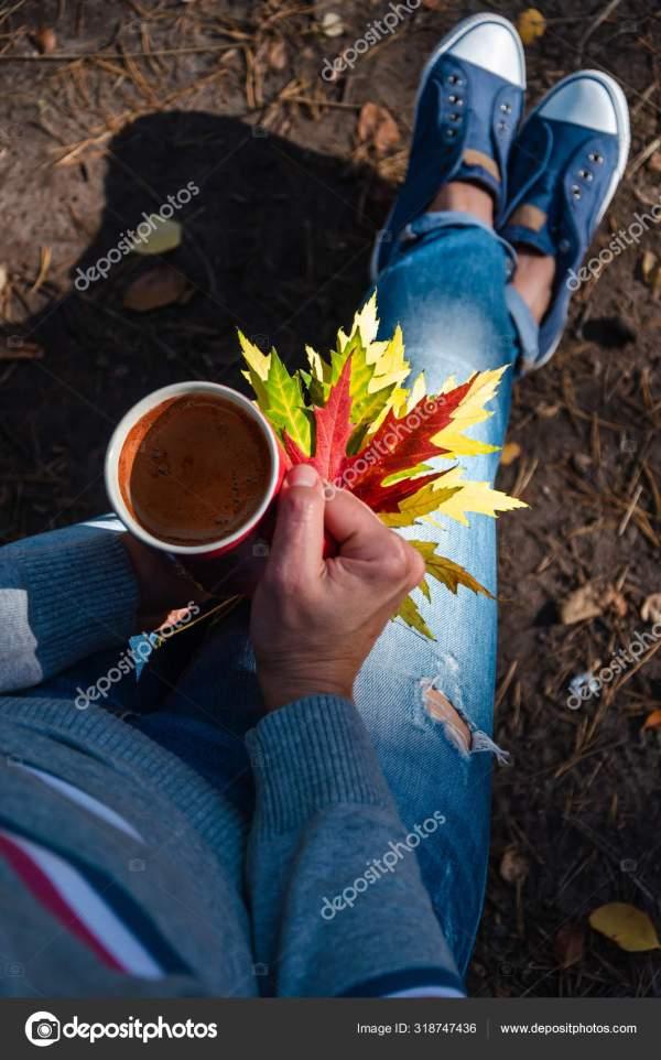 Девушка сидит на улице с кружкой кофе и красочными ...