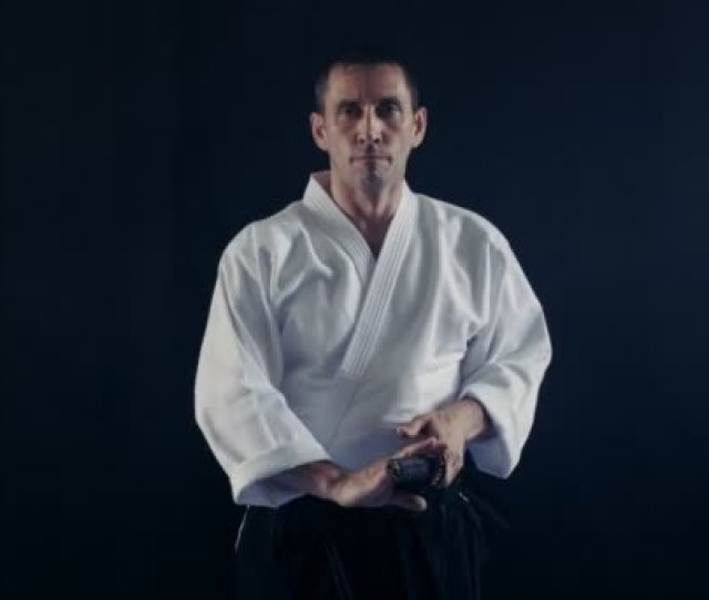 Portrait Shot Of The Aikido Master Wearing Traditional Samurai Hakama Clothes Takes His Japanese Sword Out Of Scabbard And Swings With It Hes In The