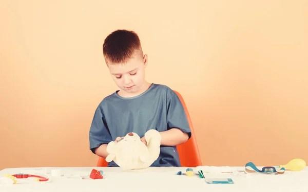 Інтерн педіатора. Маленький хлопчик у медичній формі ...