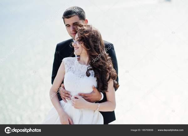 Свадебная пара на захватывающем пейзаже с камнем и озером ...