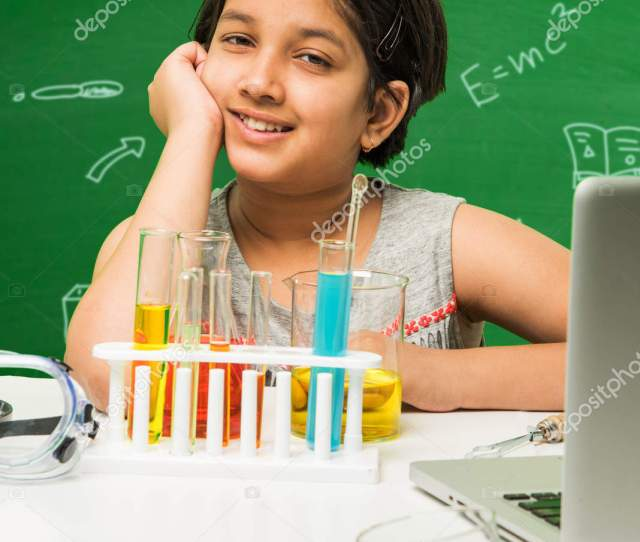 Kids And Science Concept Cute Indian Little Girl Busy Doing Science Or Chemistry Experiment With Test Tube And Flask With Safety Eye Glass Over Green