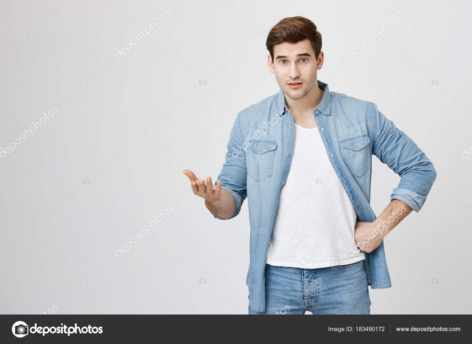 portrait interieur de beau mec avec une coupe de cheveux tendance debout en attendant la position gesticulant et tenant la main sur la taille