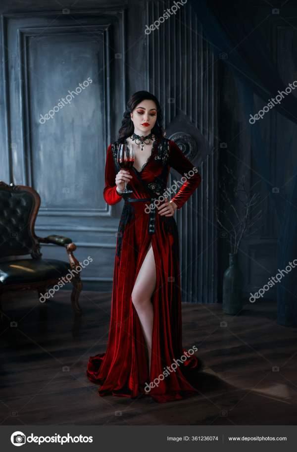 Средневековая молодая женщина-вампир держит в руке бокал ...