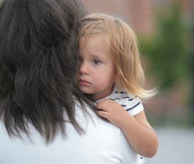 A Sad Daughter Hugging Mother Outdoors Back View Of The Brunette Mom With Her Kid Little Girl With Frustrated Face Embracing Young Woman Outside