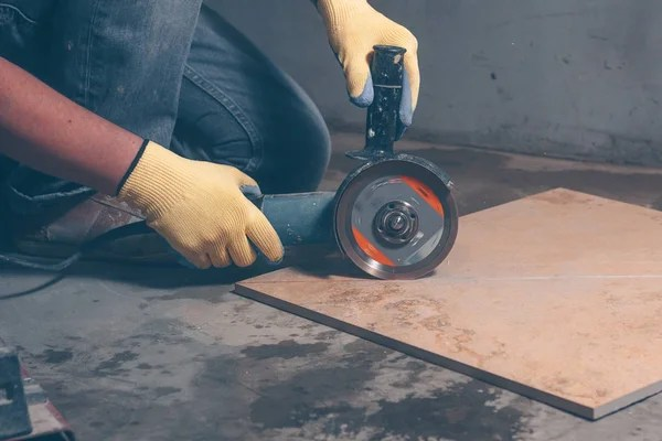worker in gloves uses angle grinder for