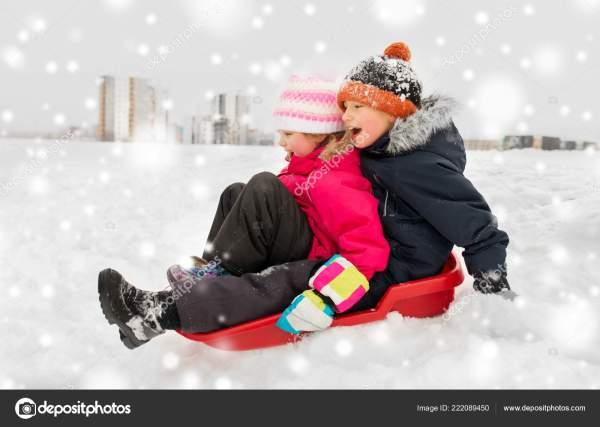 Маленькие дети катаются на санках вниз по холму зимой ...