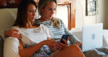 Lesbian Couple Using Mobile Phone Laptop Bed Home