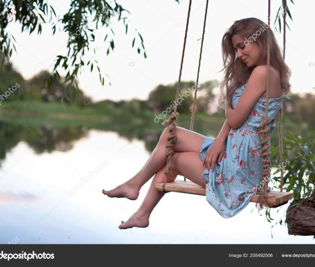 Sexy Woman Swinging On The Swing Outdoor Hair Free Legs Stock Photo