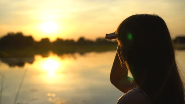 Young beautiful woman looking at sunset by the lake, smiling, enjoying view  — Stock Video © SynthEx #256758426