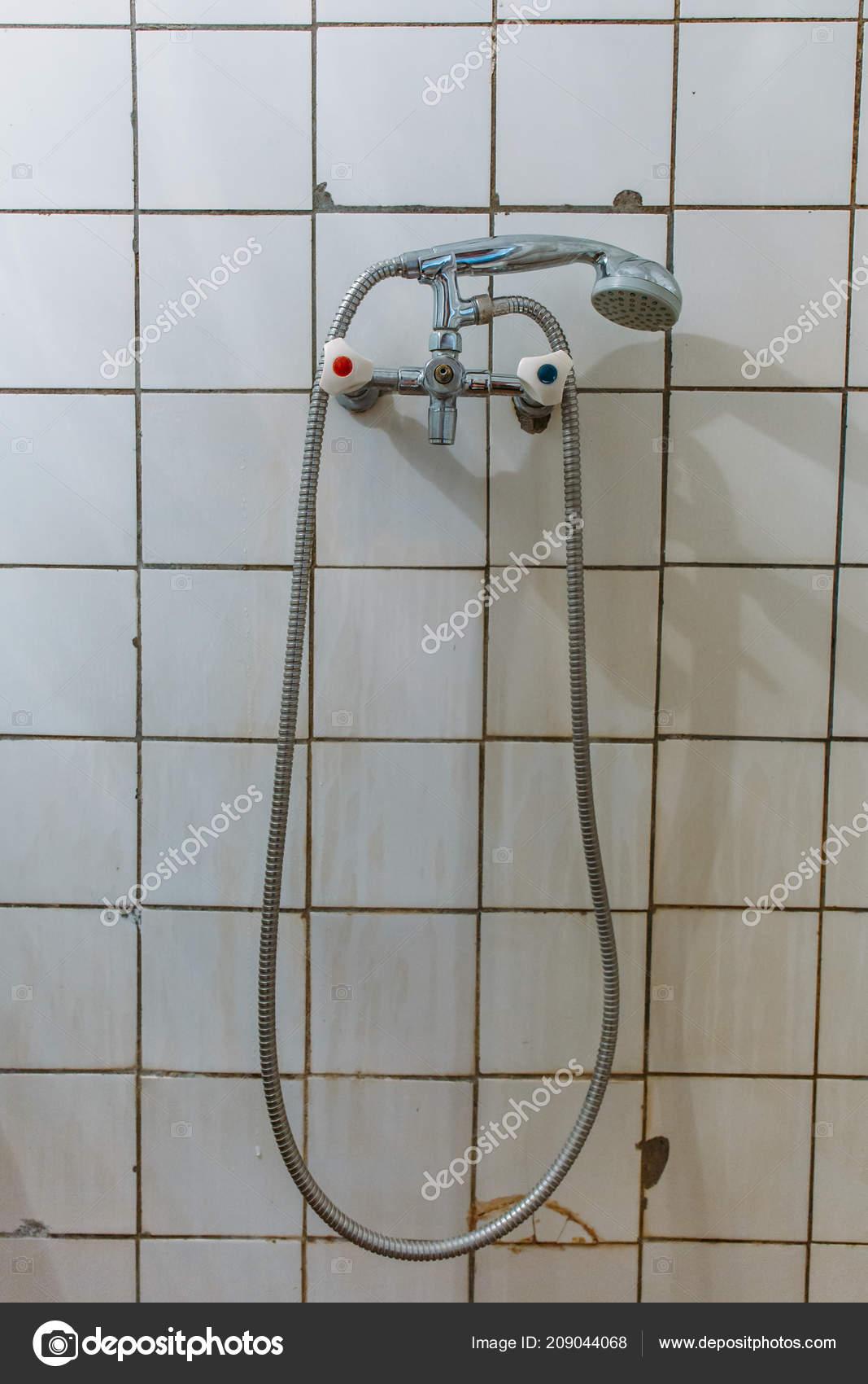 Old Steel Shower Faucet At White Vintage Tile Background