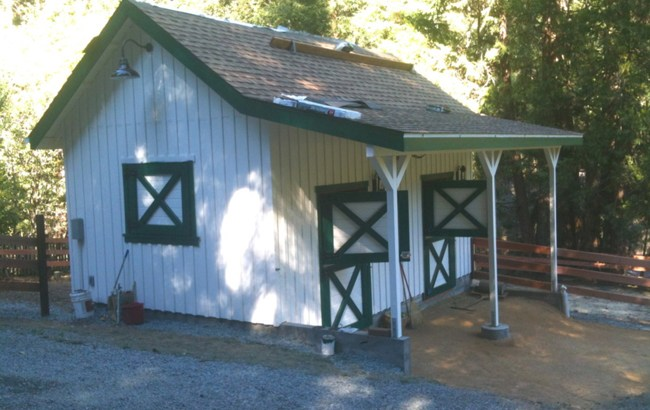adorable two stall barn with dutch doors and over hang