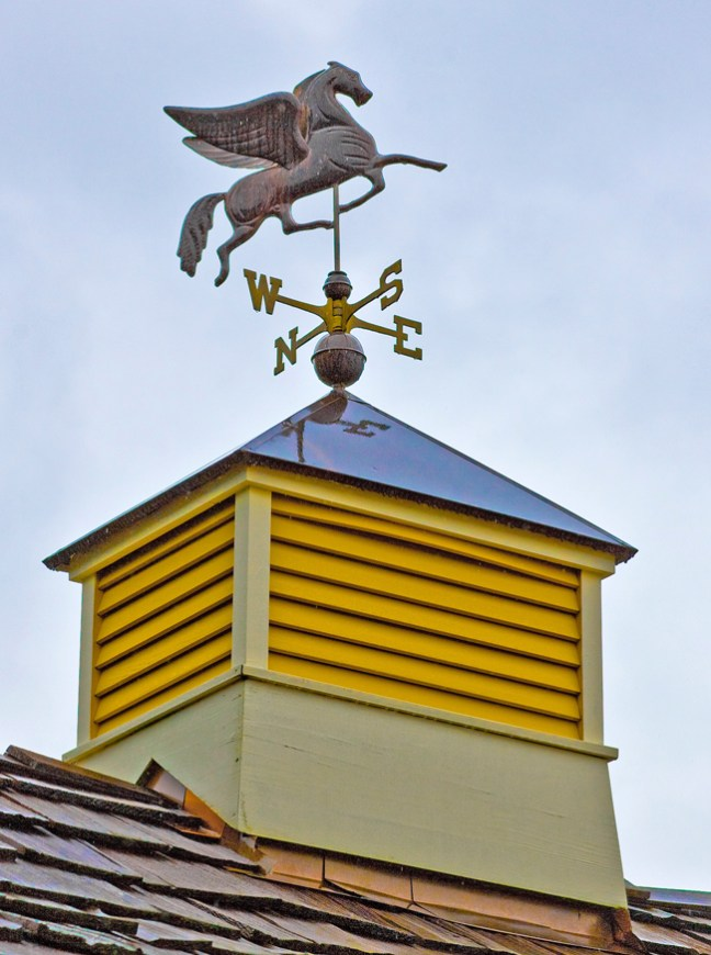 horse weather vane on a yellow cupola