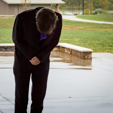 Groom bent over in joy after seeing his bride for the first time.