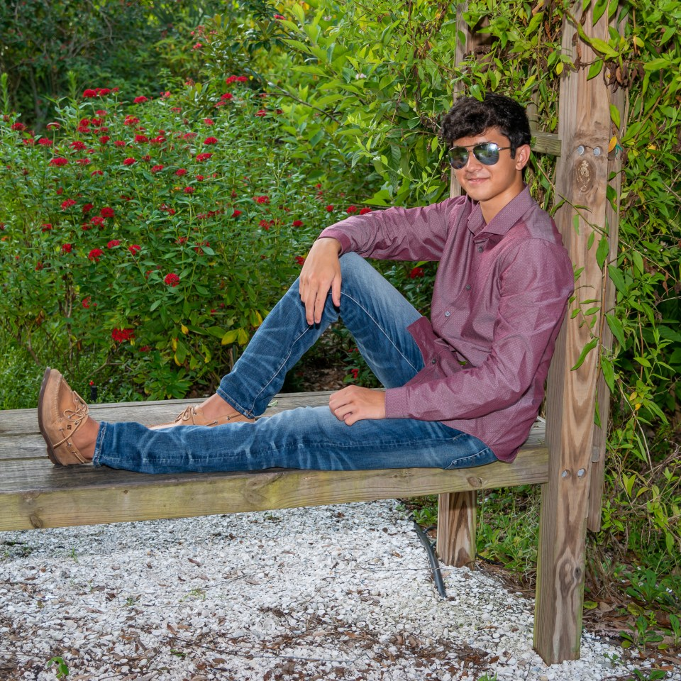 A high school senior lounges on a bench in his sunglasses surrounded by bushes for his senior pictures.
