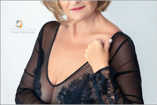 A woman in black lingerie on a white background poses for a boudoir session.