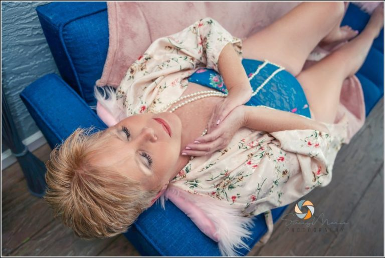 An older woman lays on a couch and poses for her boudoir session.