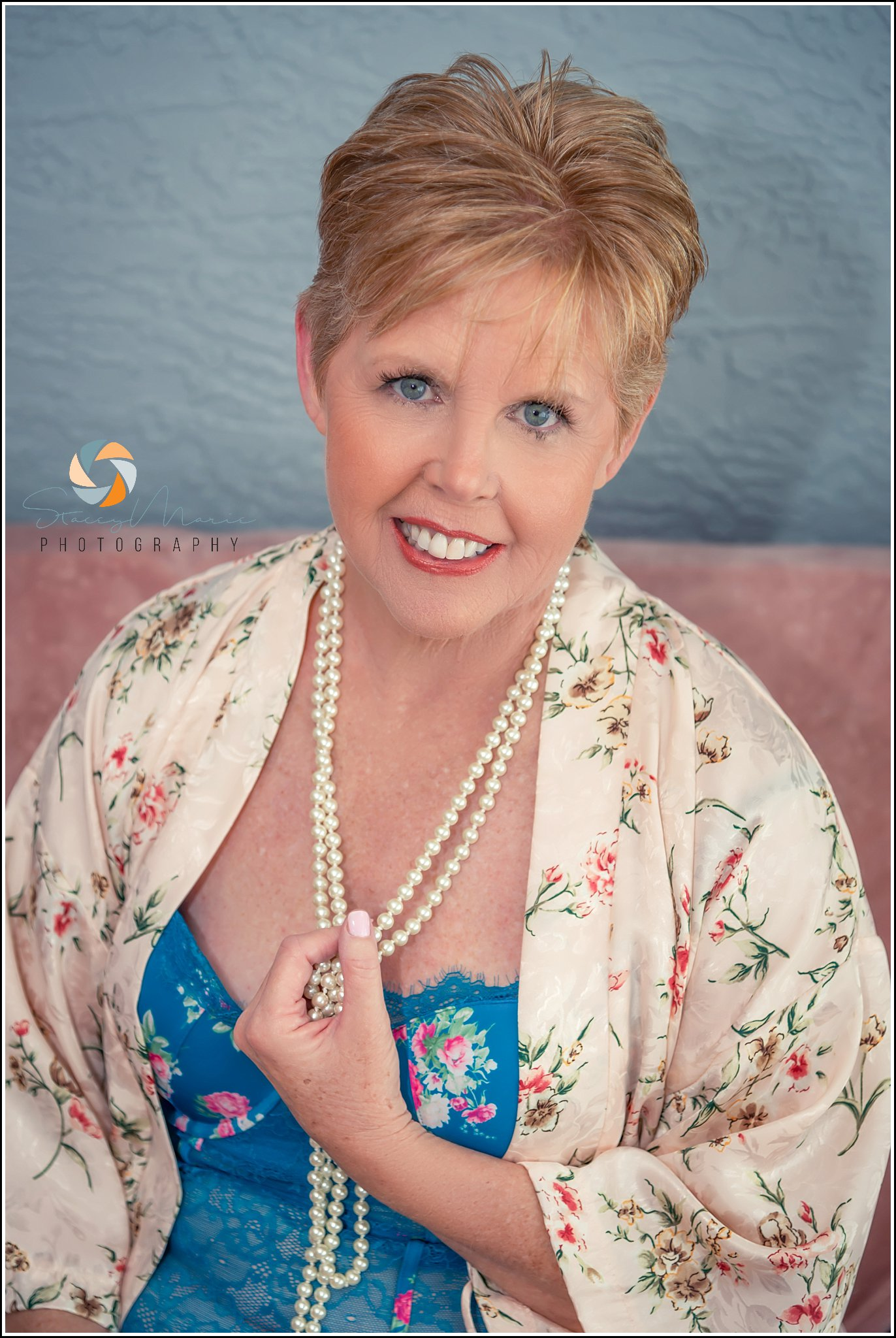 An older woman poses in lingerie and pearls for her boudoir sesision.