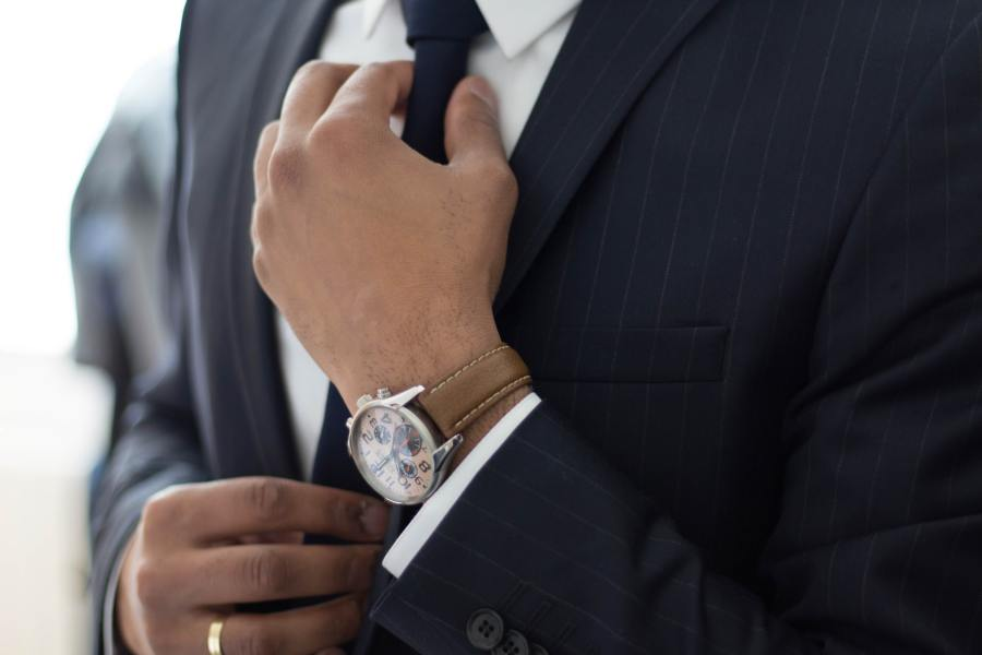 Close up of a man in a business suit straightening his tie. Representative of the false image of a professional 'look'.